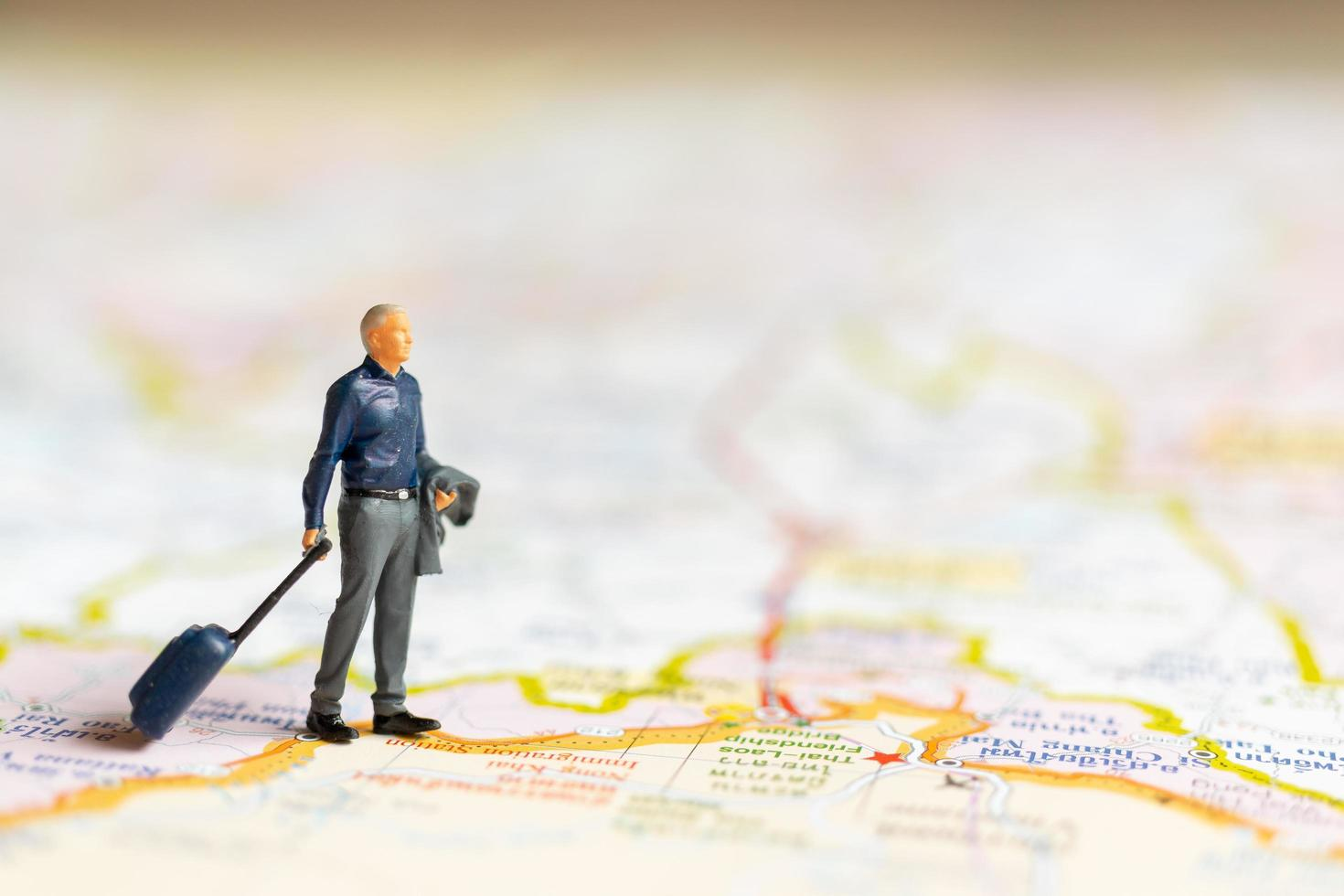 Miniature businessman standing on map, travel concept photo
