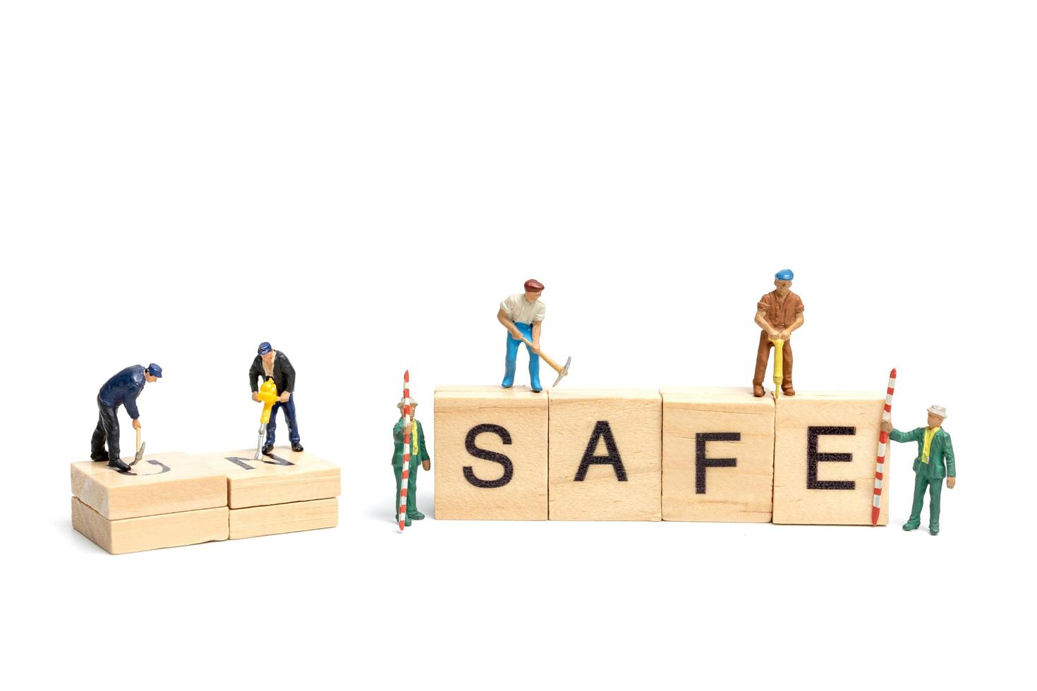 Miniature people, team of workers changing the word Unsafe turned into Safe on white background photo