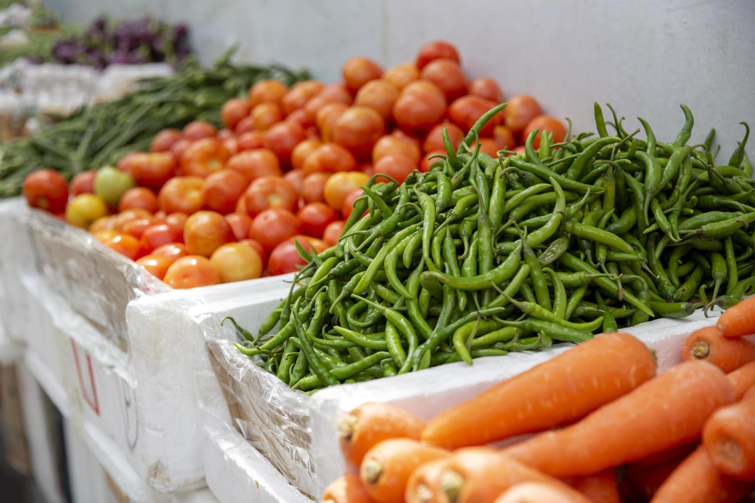 Grupo de tomates frescos y verduras orgánicas antecedentes en el mercado foto