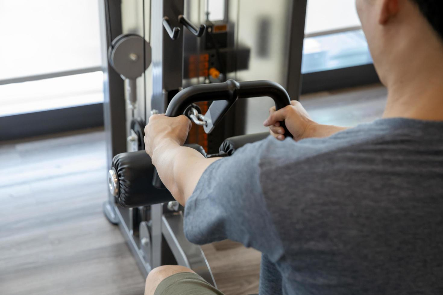 Young man beginner exercising with dumbbells flexing muscles at a gym, sports training concept photo