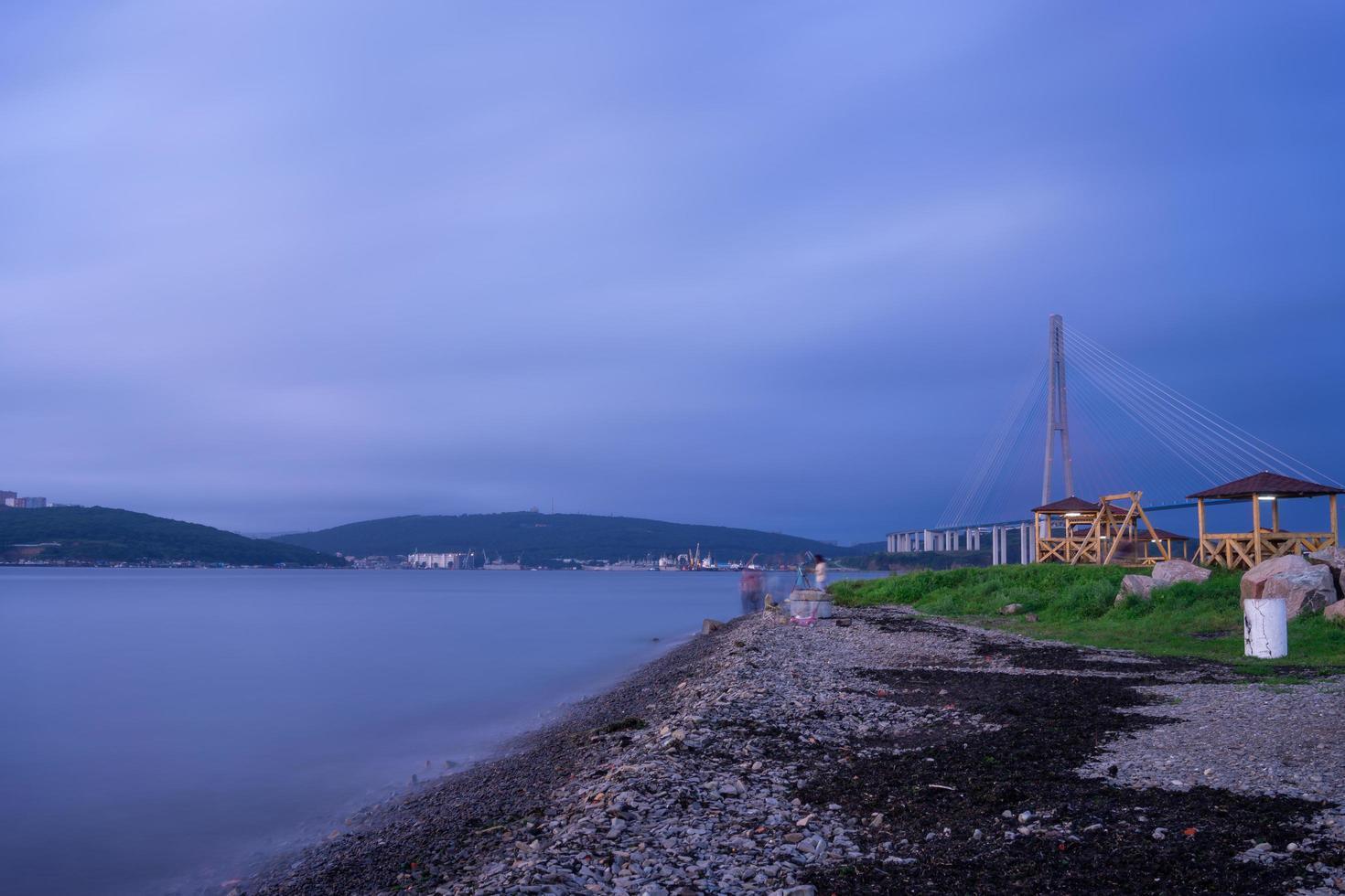 Vista de la costa rocosa con el puente russky en el fondo y un cuerpo de agua en Vladivostok, Rusia foto