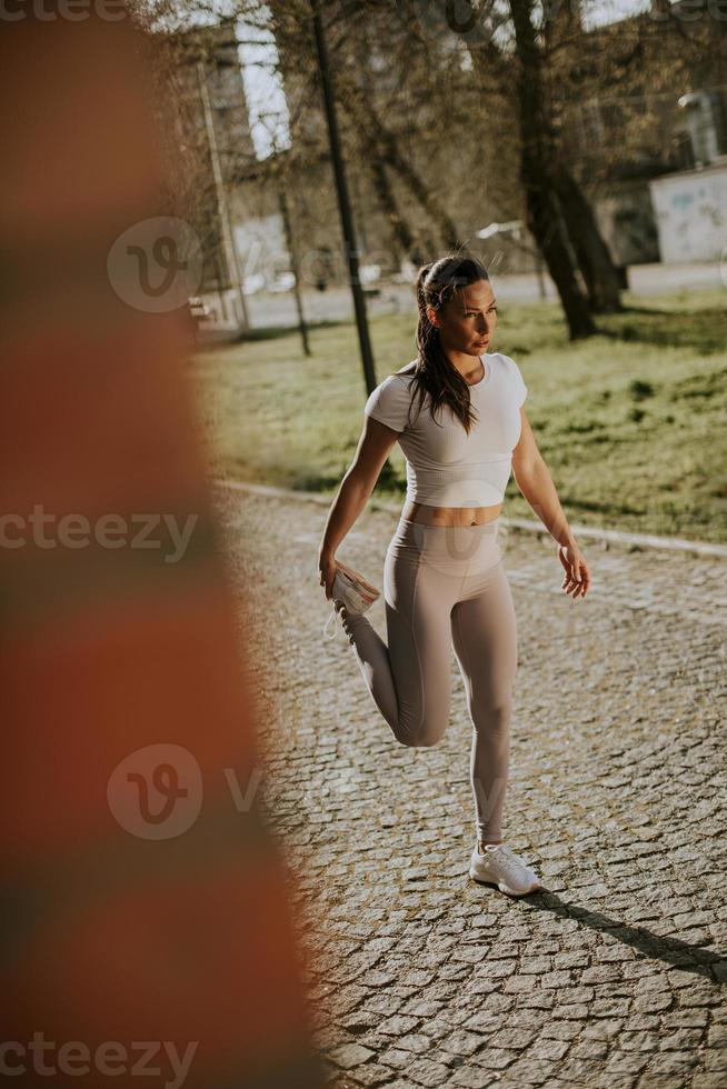 Pretty young woman stretching during training in the urban environment photo