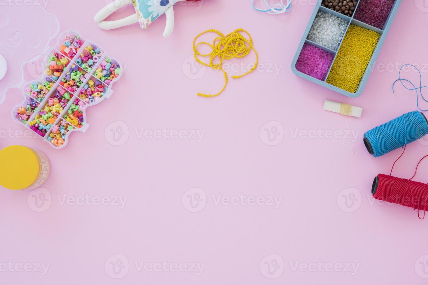 Colorful beads and case of yarn spools on pink background photo