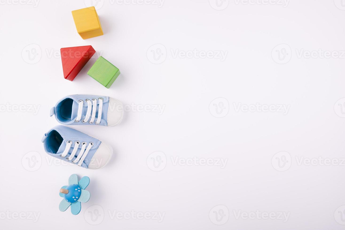 Baby shoes and toys with copy space photo