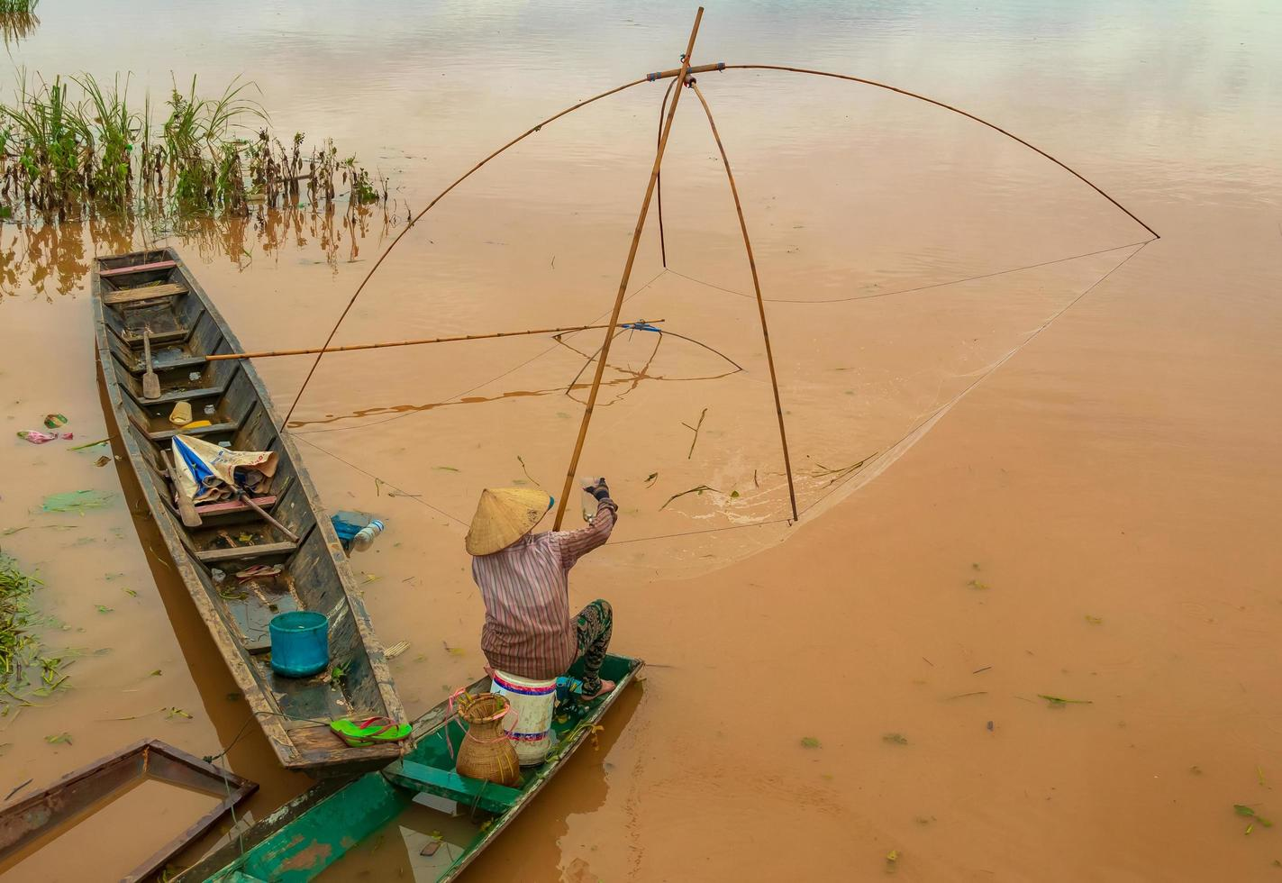 Fisherman in the Mekong with ancient fishing tools photo