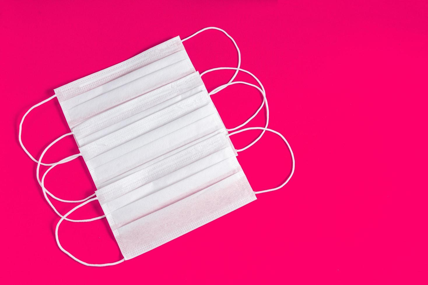 mascarilla quirúrgica sobre fondo rosa minimalista foto