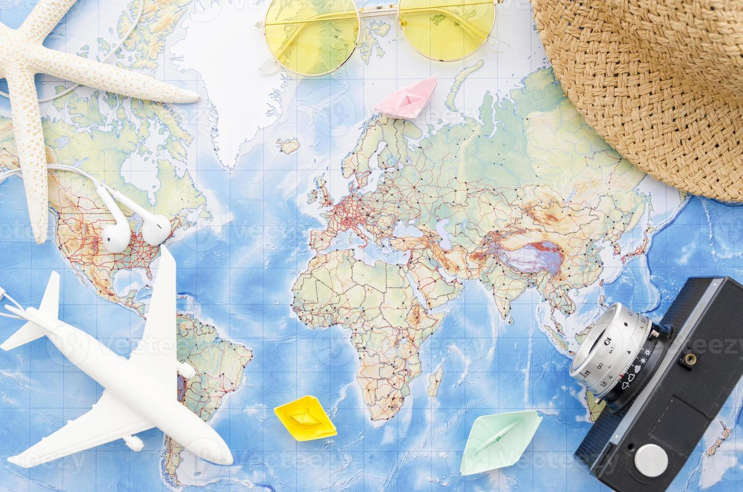 World map with camera, toy plane and starfish photo