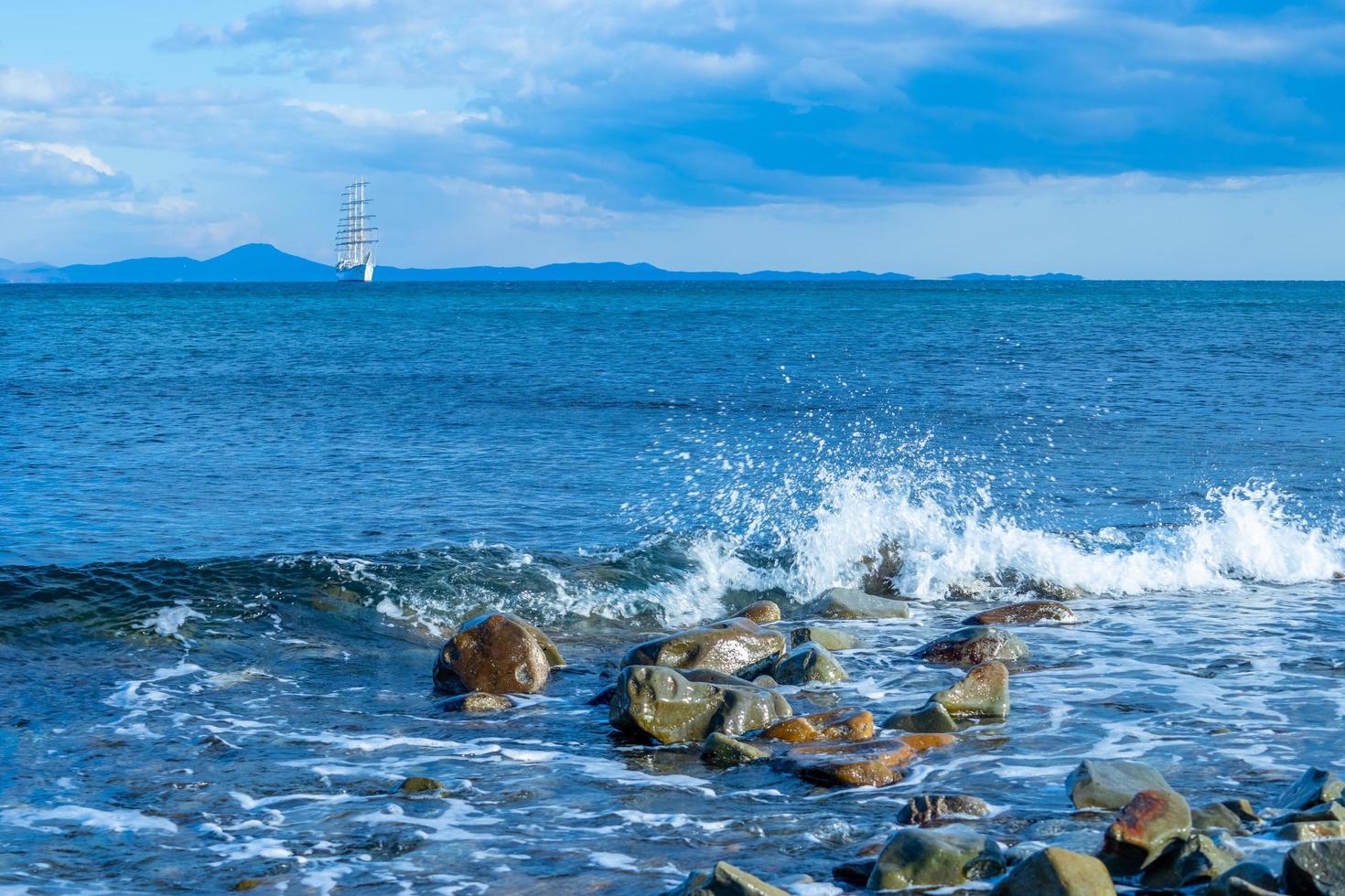 paisaje marino con un hermoso velero en el horizonte. foto