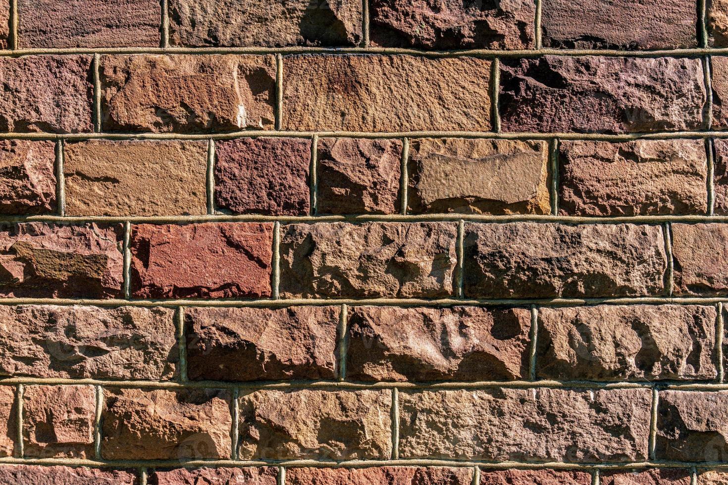 Fondo de una antigua pared de roca con piedras rosas foto