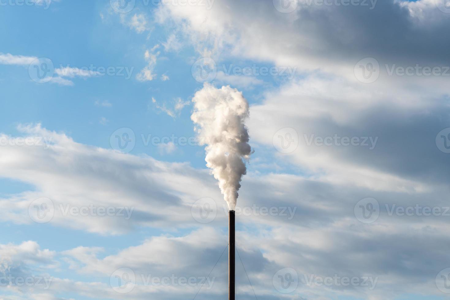 Chimenea en lo alto del aire contaminando la atmósfera. foto