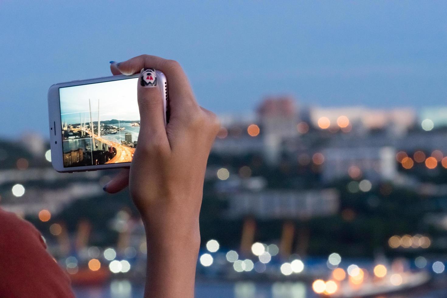 mano de niña con un teléfono inteligente tomando fotografías del puente dorado. Vladivostok, Rusia foto