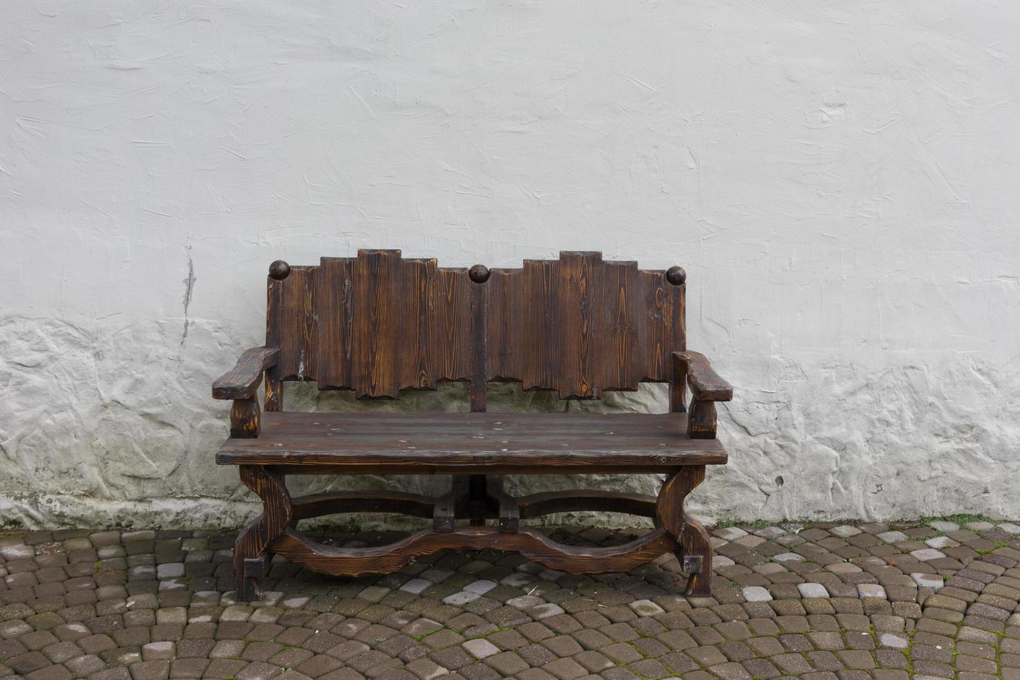 Banco de madera artesanal sobre el fondo de paredes blancas y adoquines foto