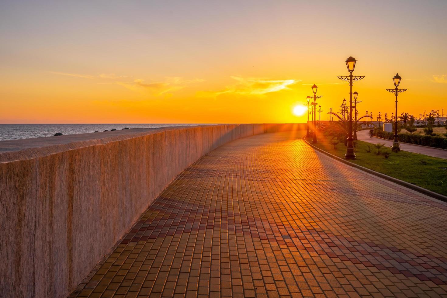 puesta de sol sobre el paseo marítimo de la ciudad turística. foto