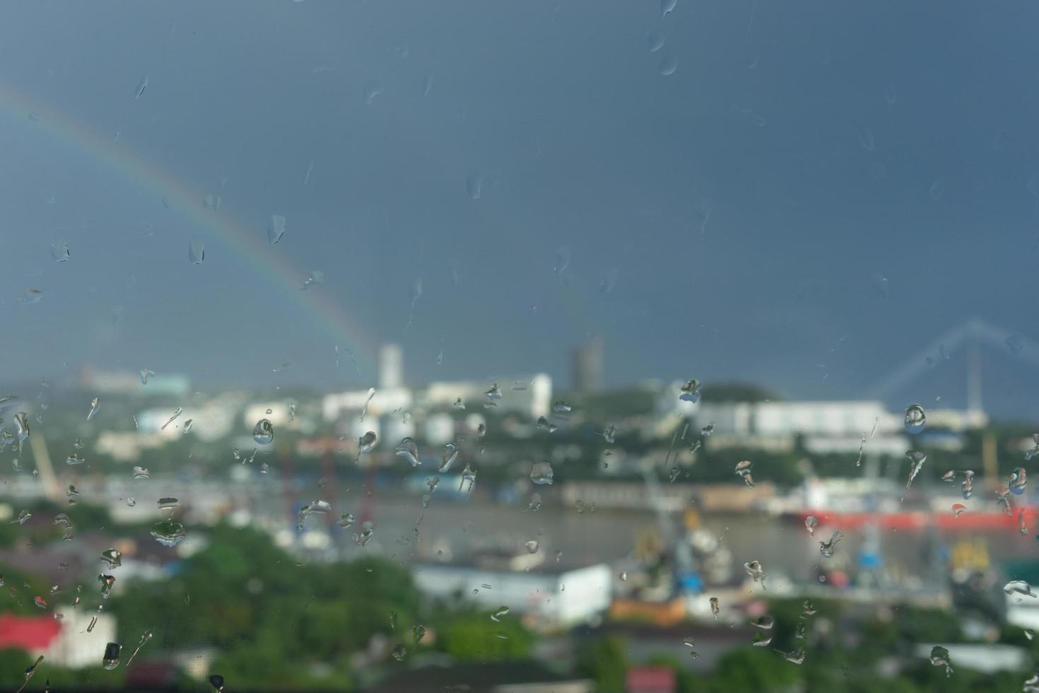 Fondo abstracto con paisaje urbano a través del cristal con gotas de lluvia foto