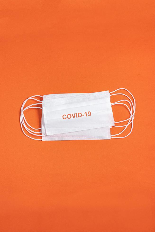 mascarilla quirúrgica sobre fondo naranja minimalista foto