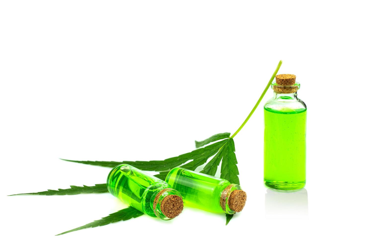 Glass bottle with CBD oil and cannabis leaf at the background photo
