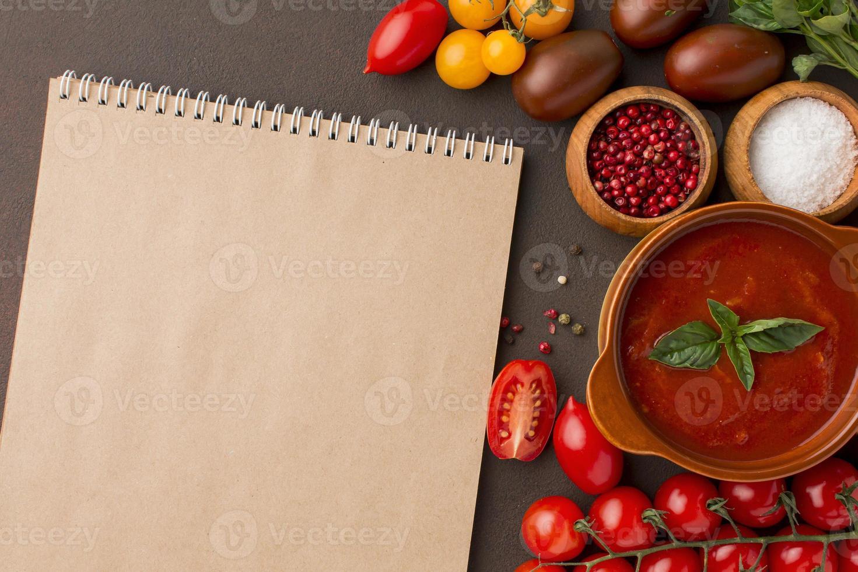 tazón de sopa de tomate de invierno de vista superior con cuaderno foto
