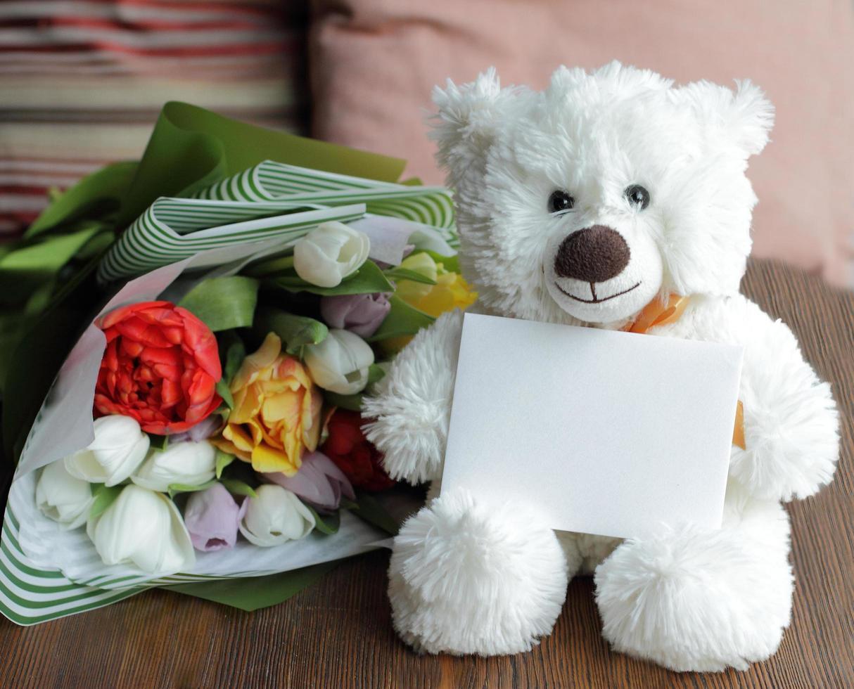 oso de peluche y tarjeta postal en blanco con ramo foto
