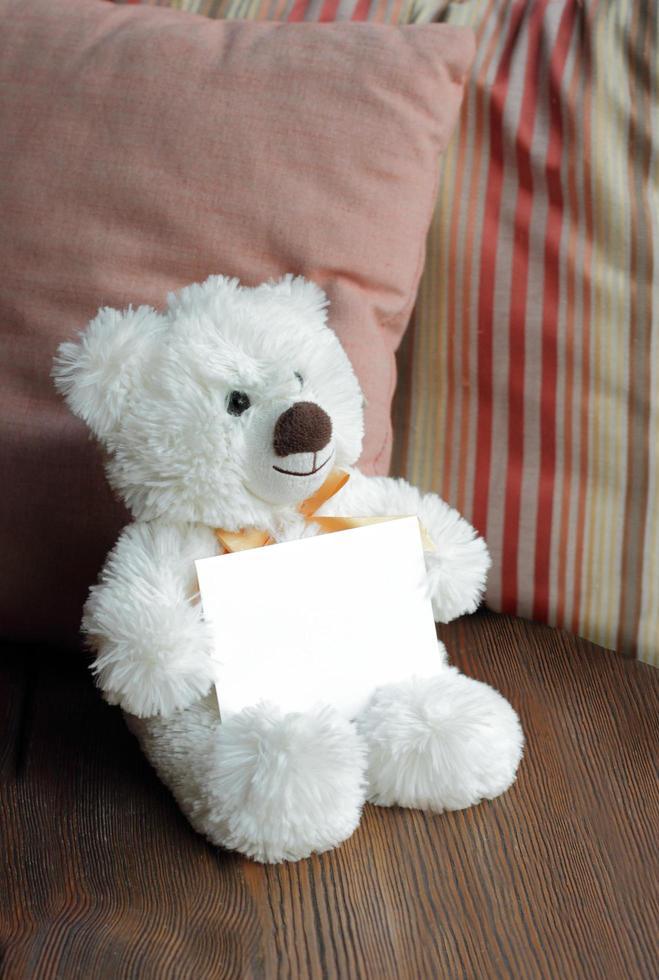 White teddy bear holding a blank notecard photo