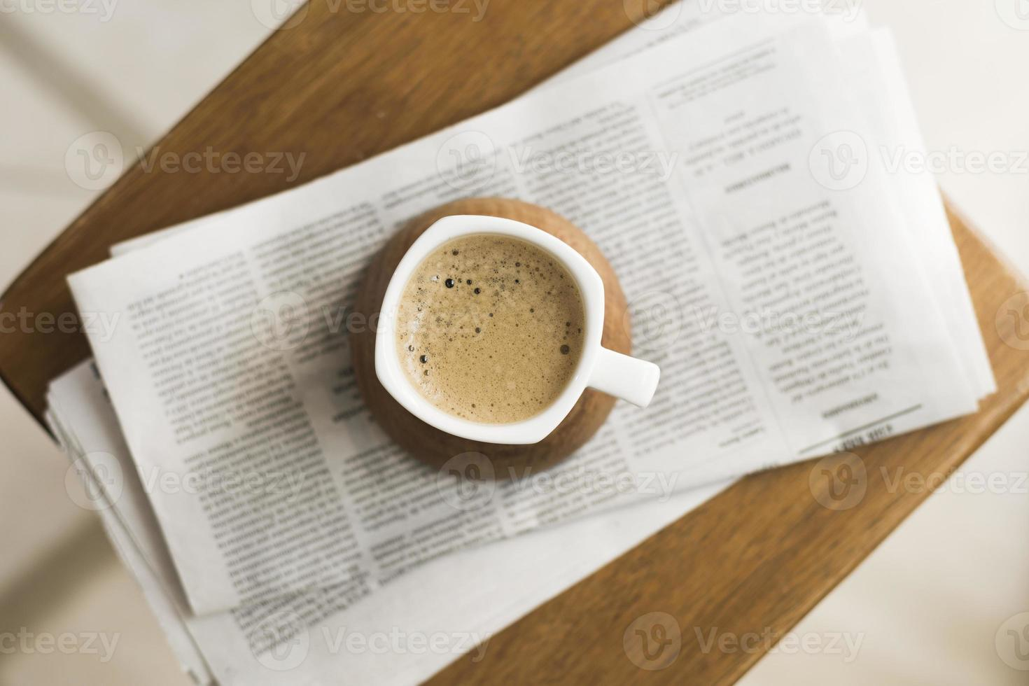 Mug with hot coffee and a newspaper photo