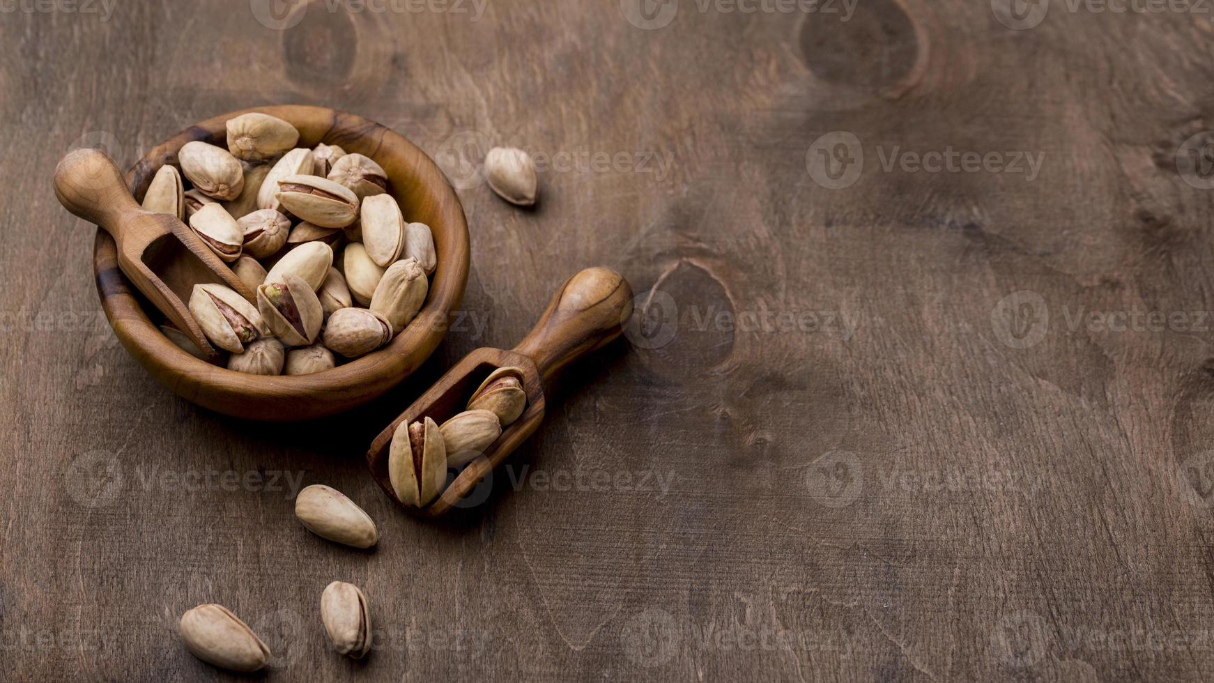 Roasted pistachio nuts on wooden table photo