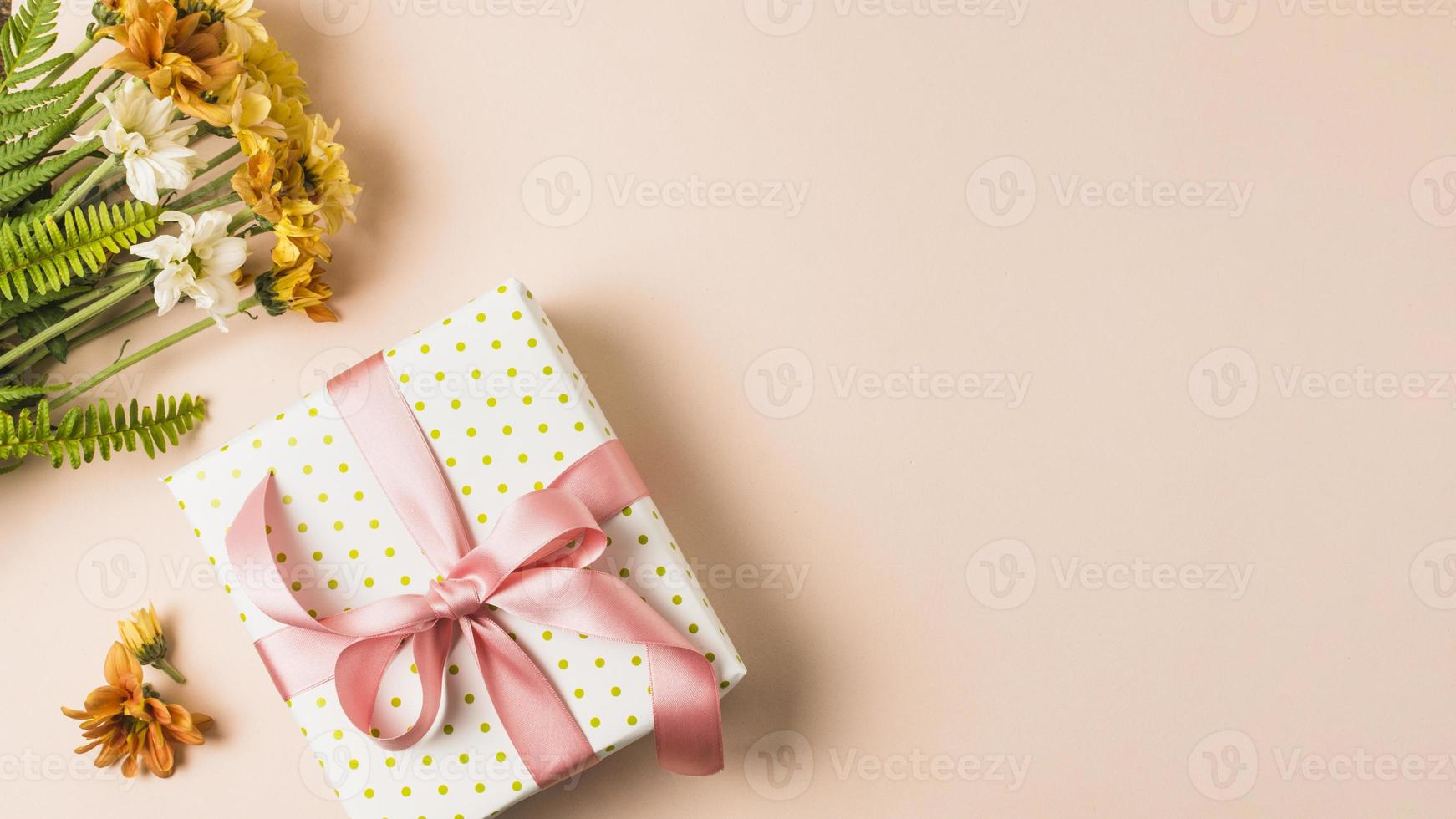 White yellow flower bouquet near wrapped present on peach surface photo