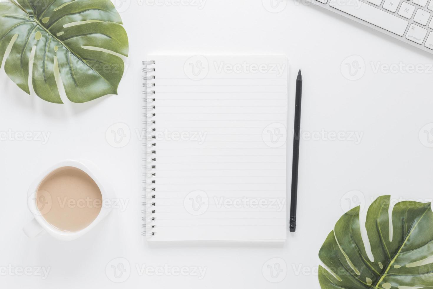 cuaderno cerca de la taza de café y el teclado con hojas verdes foto