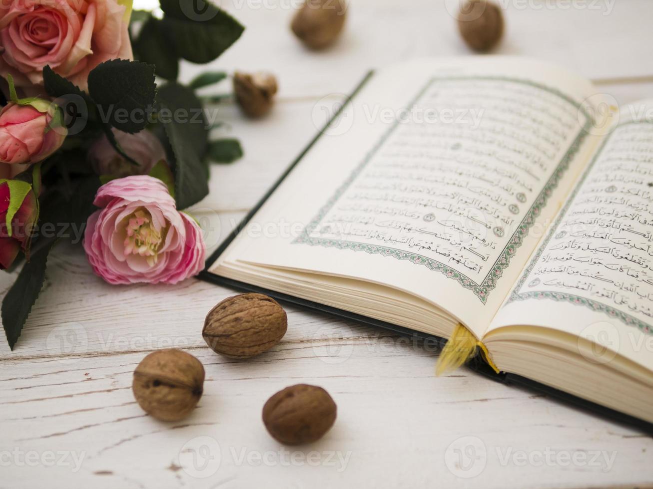 Corán abierto con rosas rosadas foto