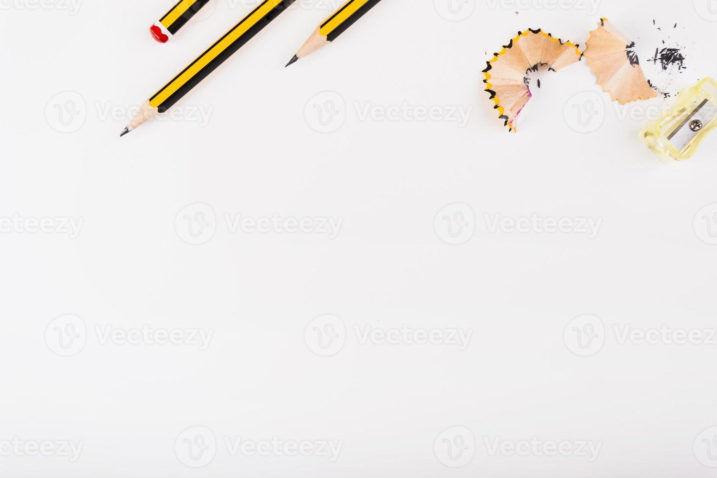 Lápices negros y amarillos y virutas de sacapuntas sobre fondo blanco con espacio de copia foto