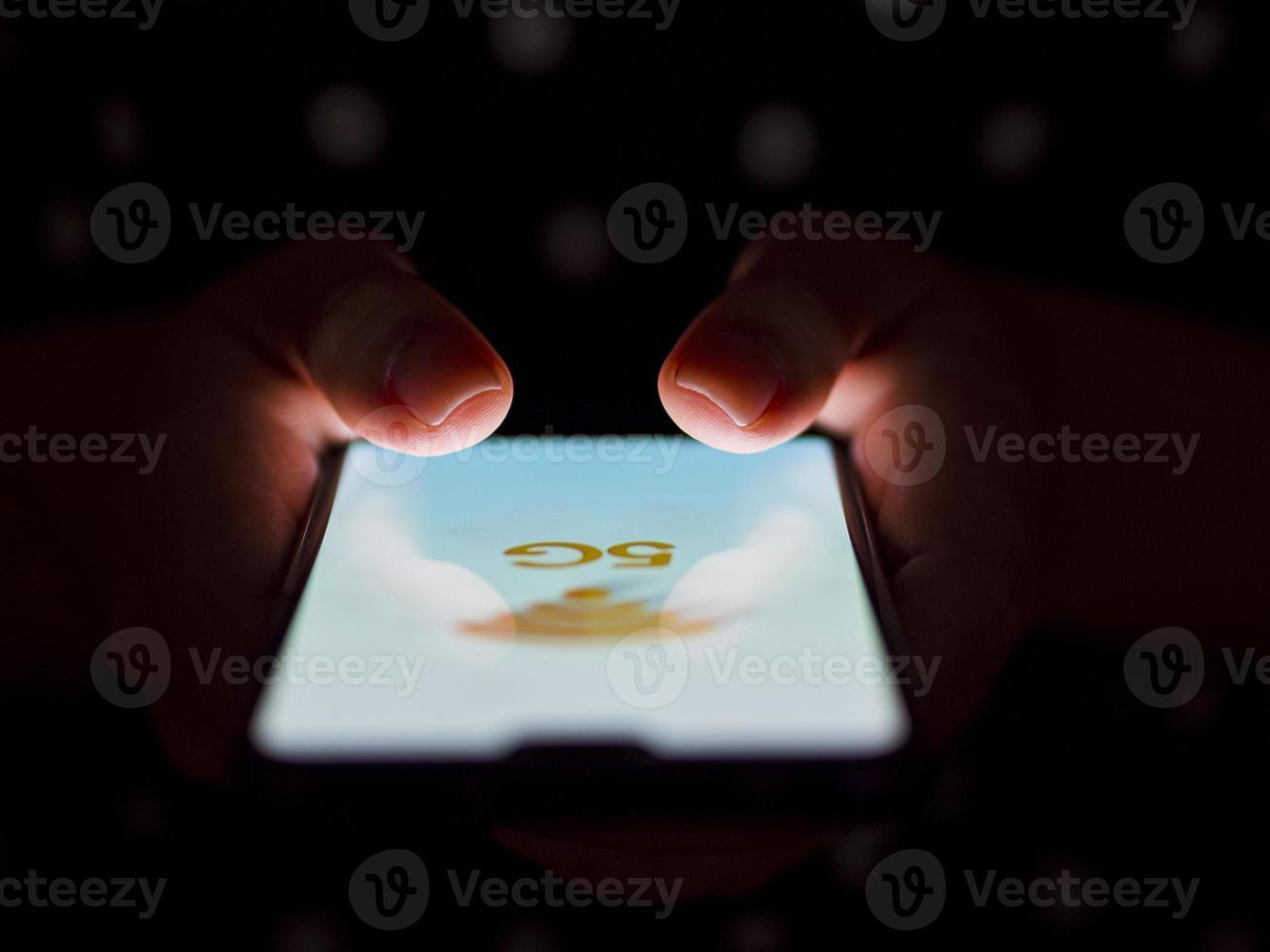 Persona que sostiene el teléfono en las manos sobre un fondo oscuro con una maqueta de 5g iluminada foto