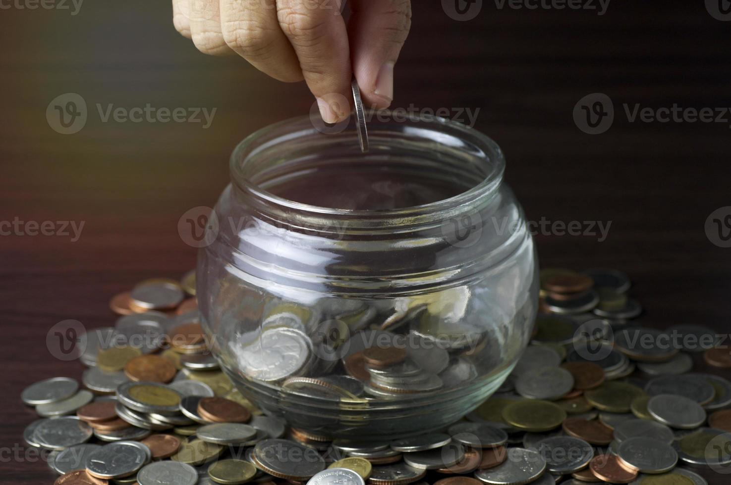 Person putting coins in a jar photo