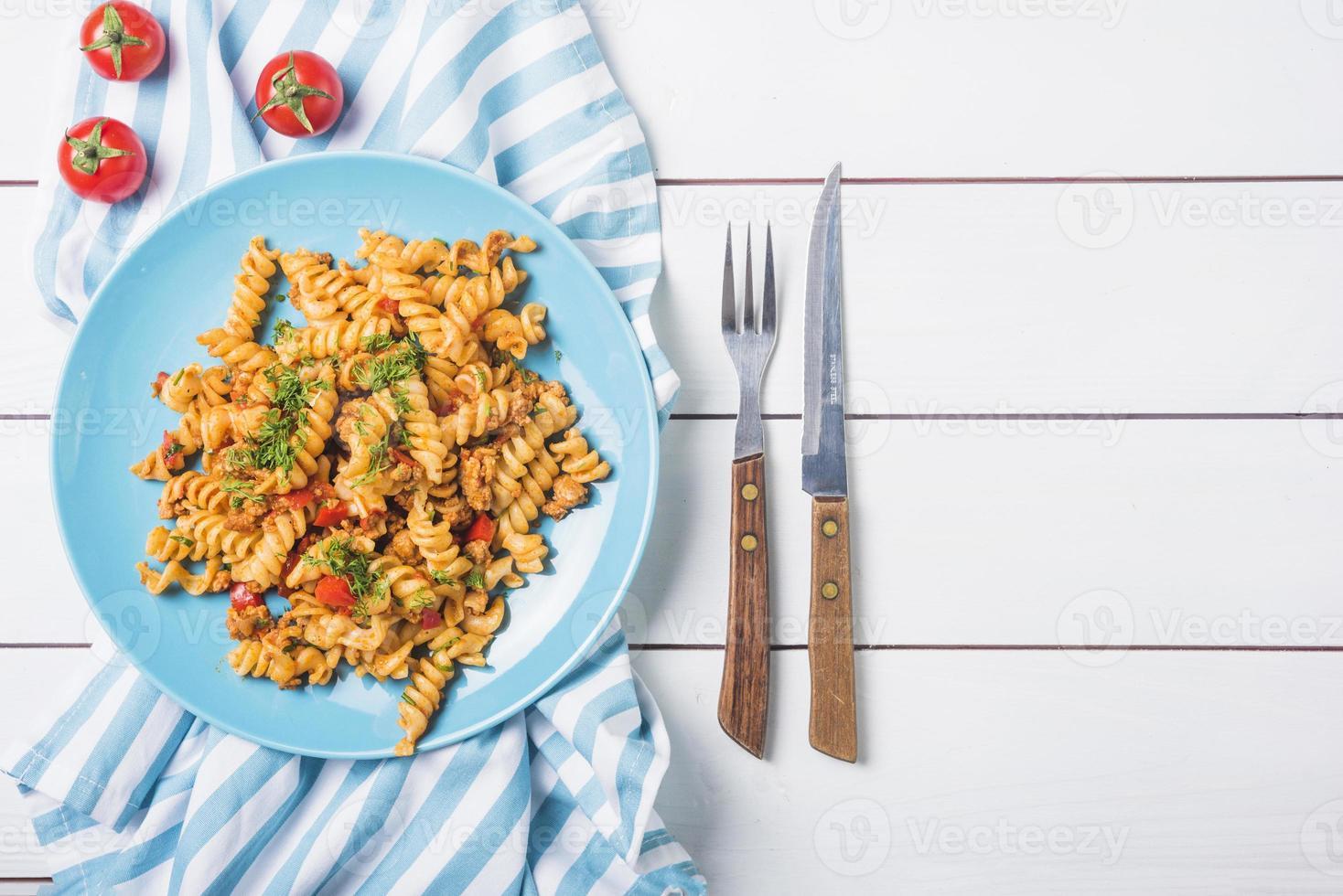 pasta fusilli con cubertería de tomate mesa de madera blanca. concepto de fotografía hermosa de alta calidad y resolución foto