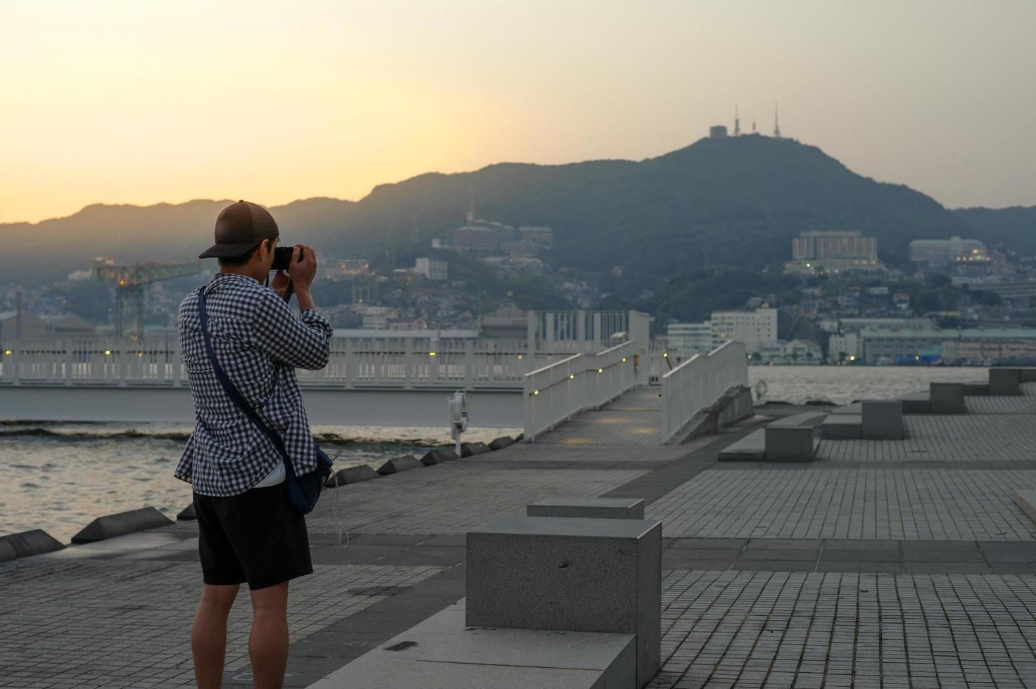 Back portrait of Asian man standing and taking the picture of landscape and cityscape photo