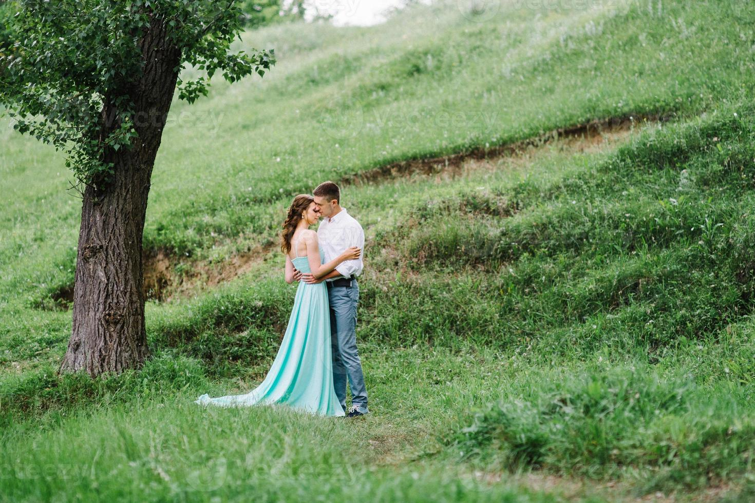 happy guy in a white shirt and a girl in a turquoise dress are walking in the forest park photo