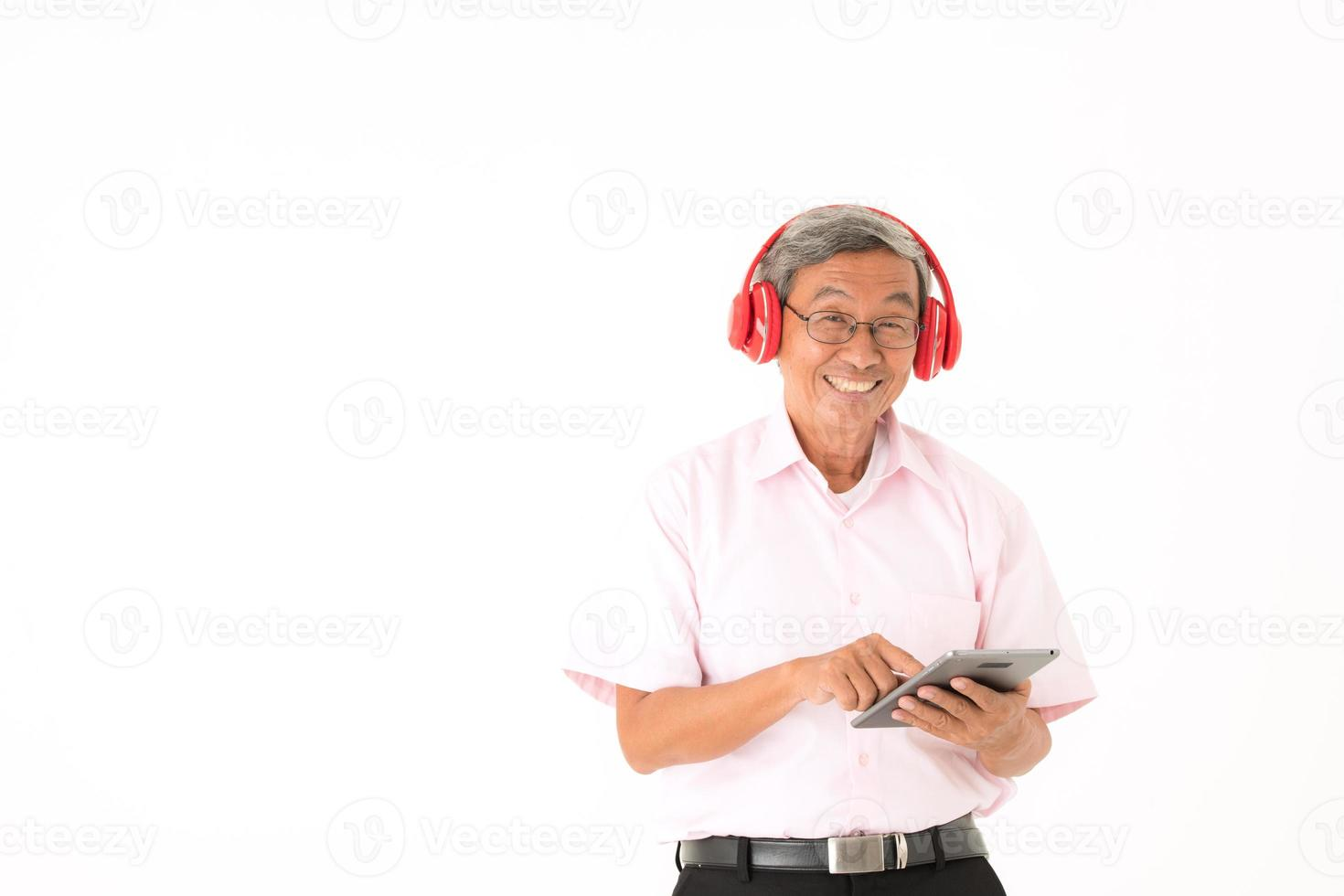 Senior Asian man happy to listen to music online with headphones and tablet, isolated photo