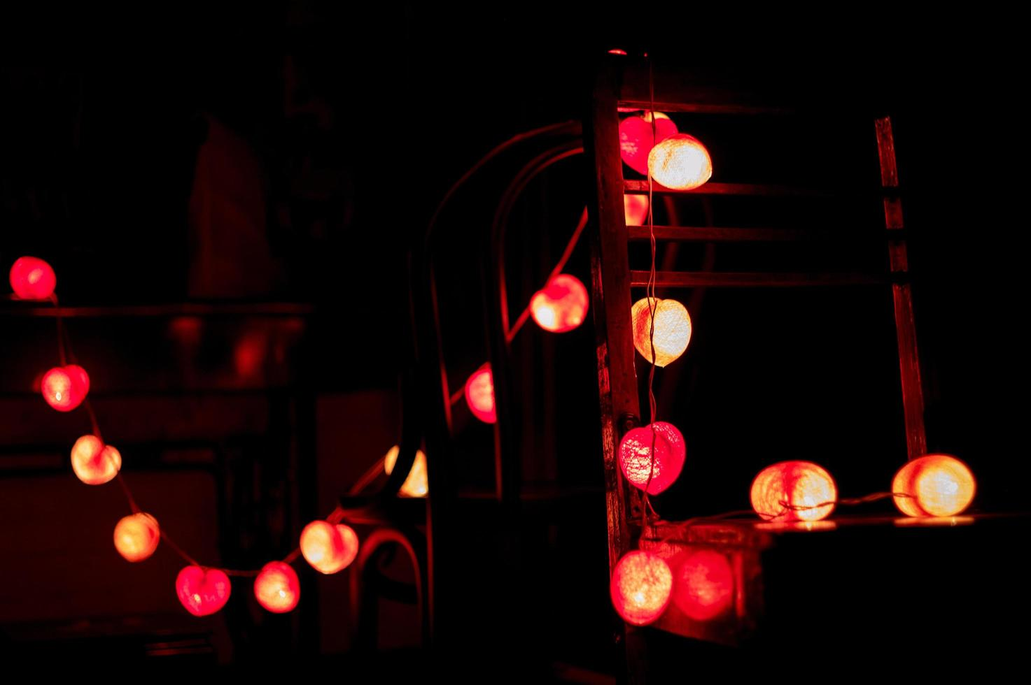 Closeup heart-shaped LED lights hanging on wooden chairs decorated in the darkroom photo