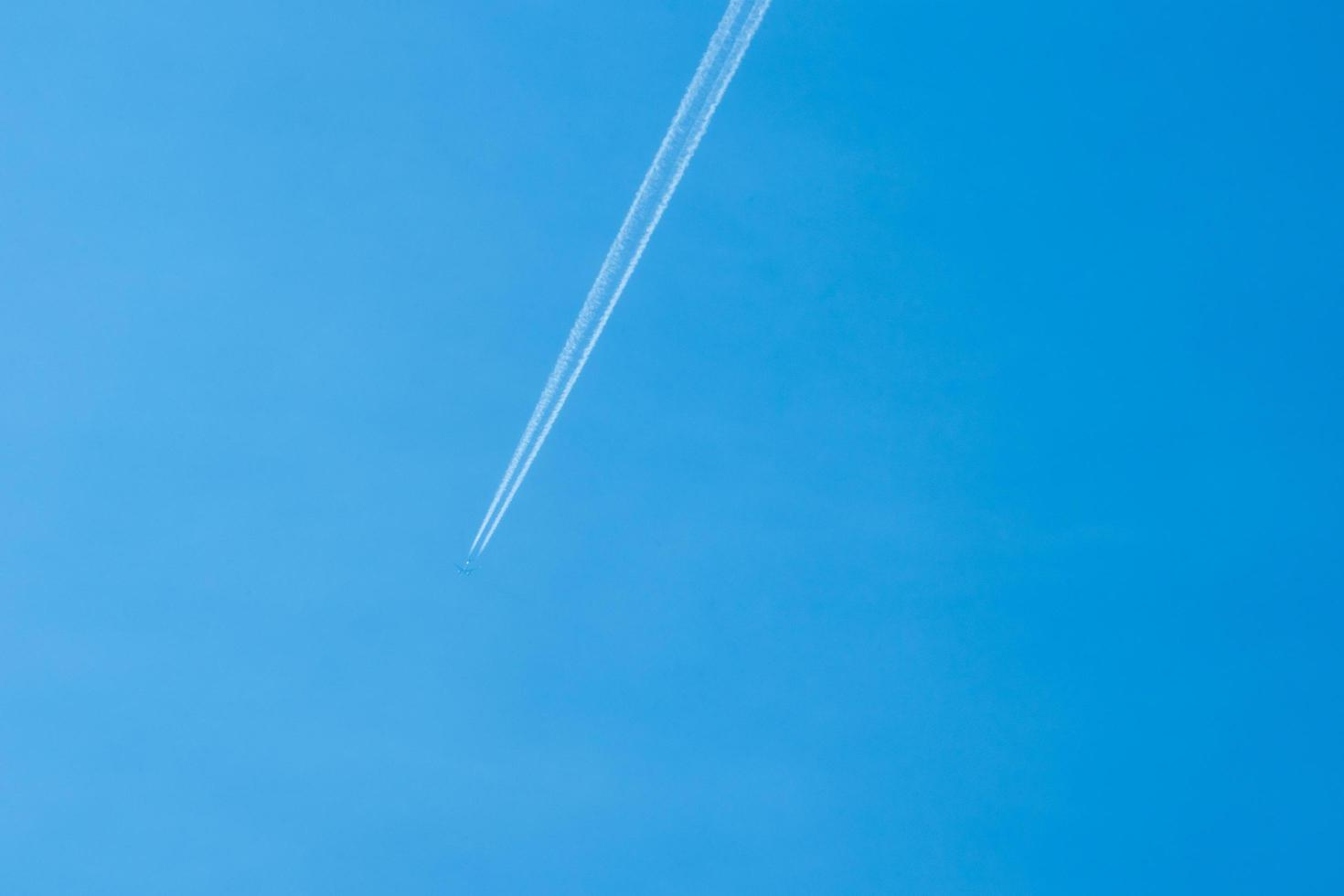 Airplane flying in the clear blue sky with white trail along the route photo