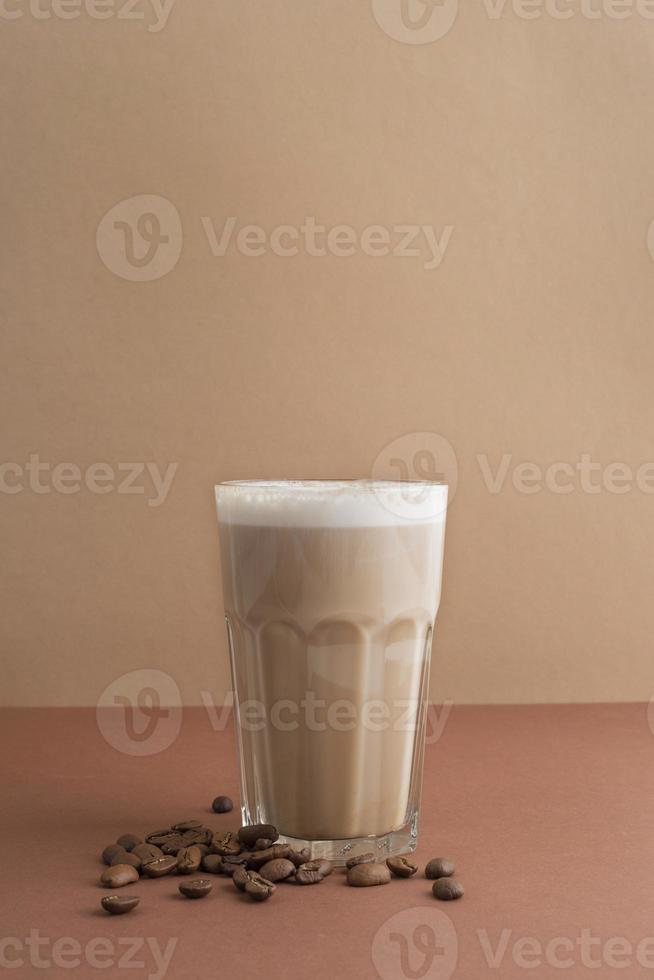 Glass of coffee with coffee beans beside photo