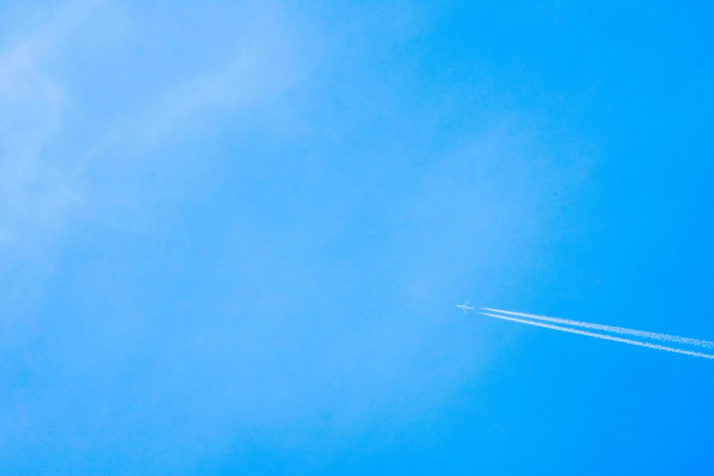 Airplane flying in the clear blue sky with white trail along the route. Jet with contrail in high speed photo