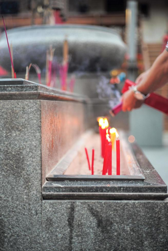 Group of red lighting candles put in the sand in concrete tray with blurred hands holding incenses photo
