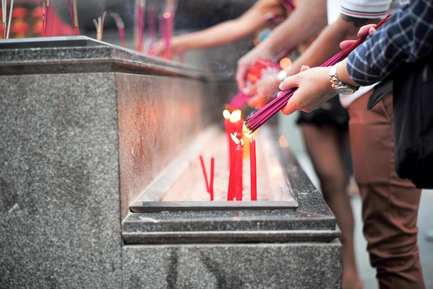 Closeup hands holding the bundle of incenses for lighting with candles in the sand tray photo