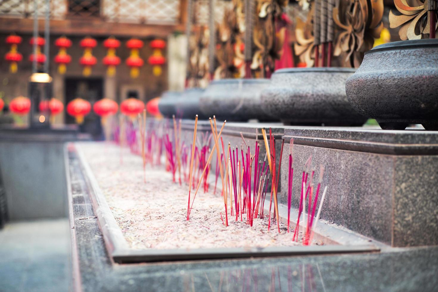 Selective focus on the bundle of fired incenses put in a sand tray with a blurred crowd of incense sticks in the background photo