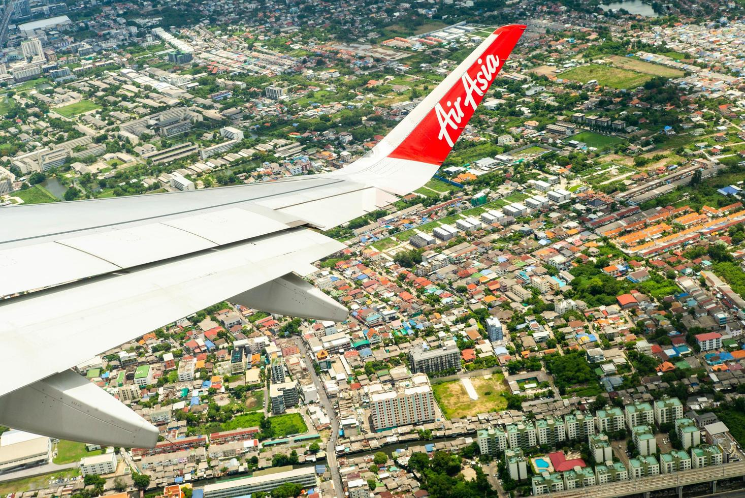 Bangkok, Thailand  - June 8, 2020 - Closeup wing of an Air Asia airplane while flying in the air with cityscape below photo