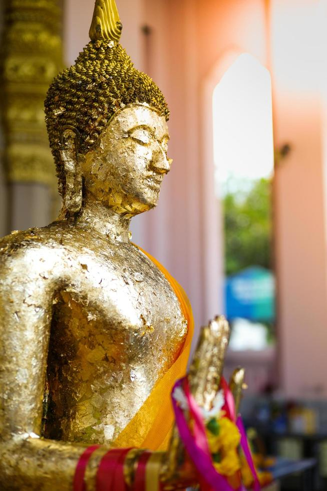 Closeup Buddhist statue coated by the golden leaf and hanging by flower garlands photo