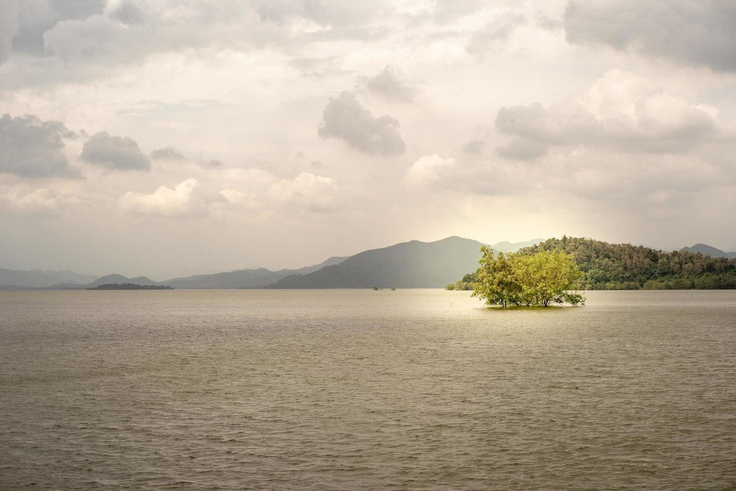 Landscape horizontal line of endless mountains and large lake with trees growing in the water. Water in the natural dam at Phetchaburi photo