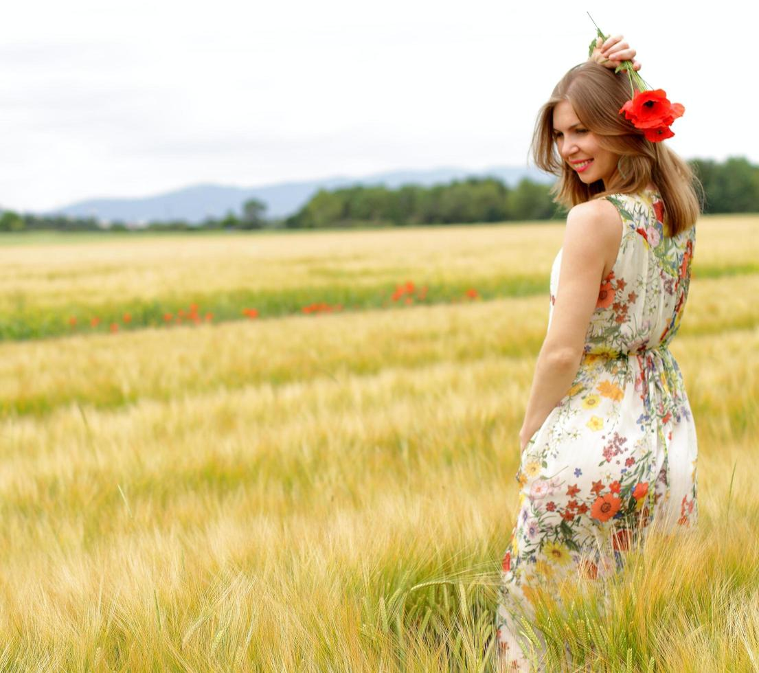 Woman posing in a floral dress in a field photo