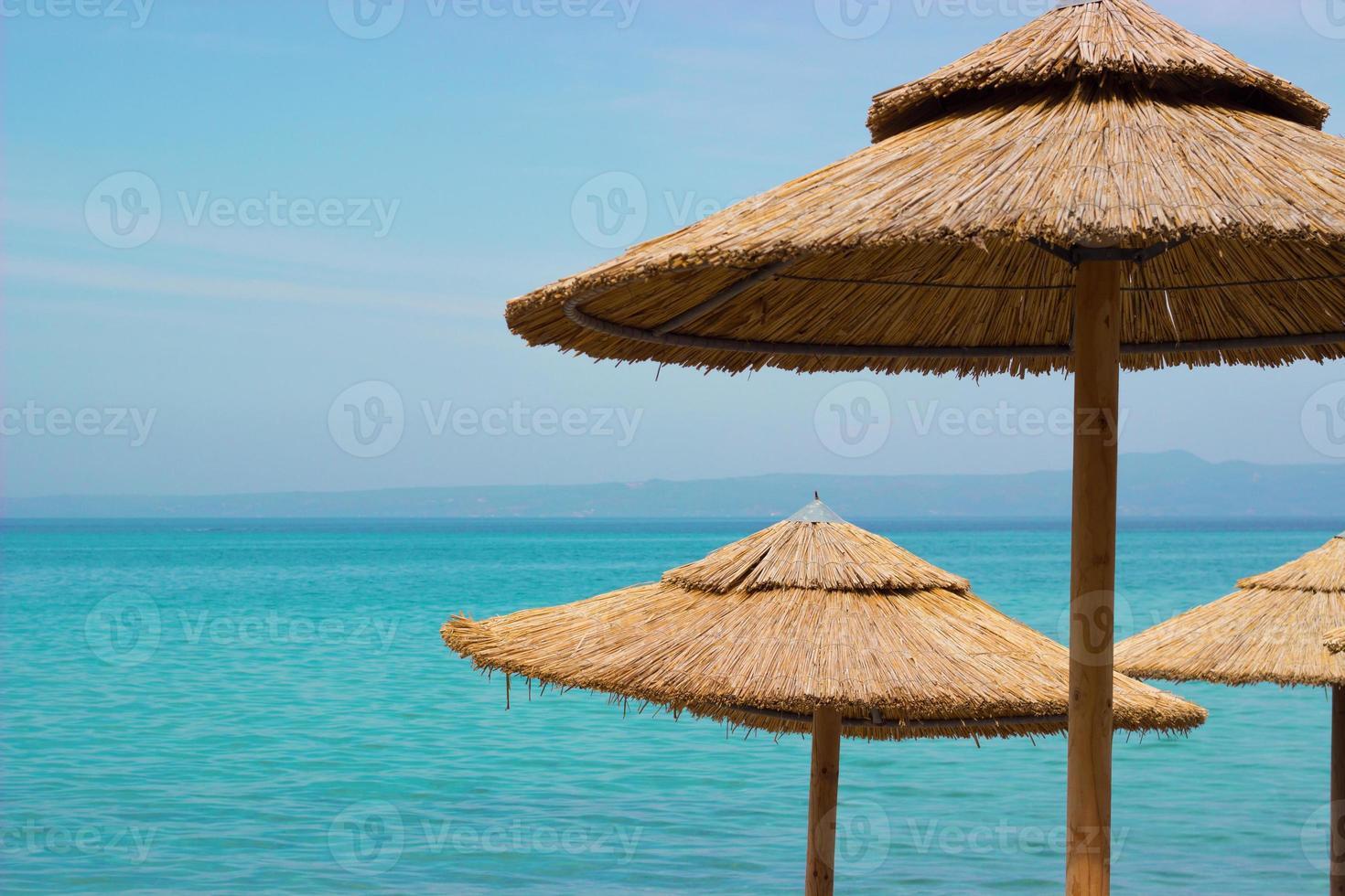 Straw sunshades on the beach photo