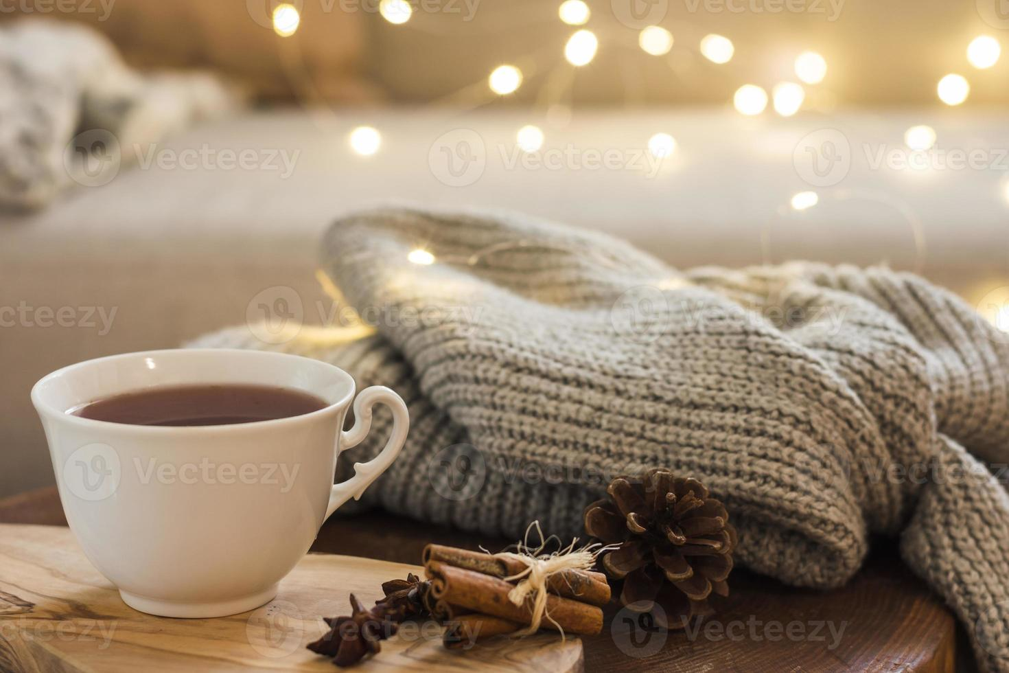 Tea cup with knitted plaid and warm lights photo
