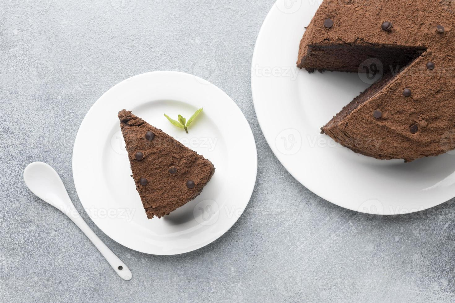 Top view chocolate cake slice with spoon and mint photo