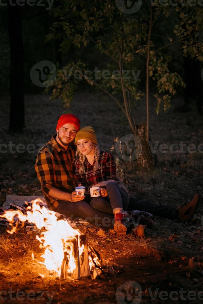 Young couple a guy and a girl in bright knitted hats stopped at a camping photo